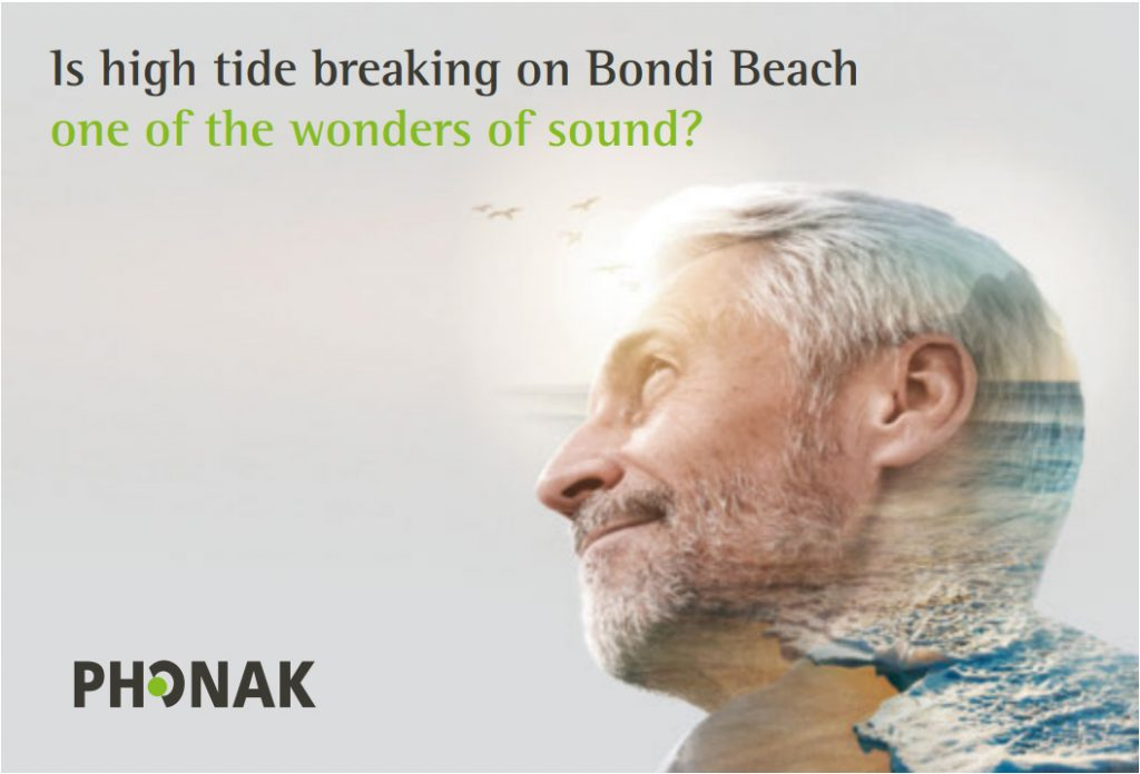 A man listening to the waves on a beach through a phonak paradise