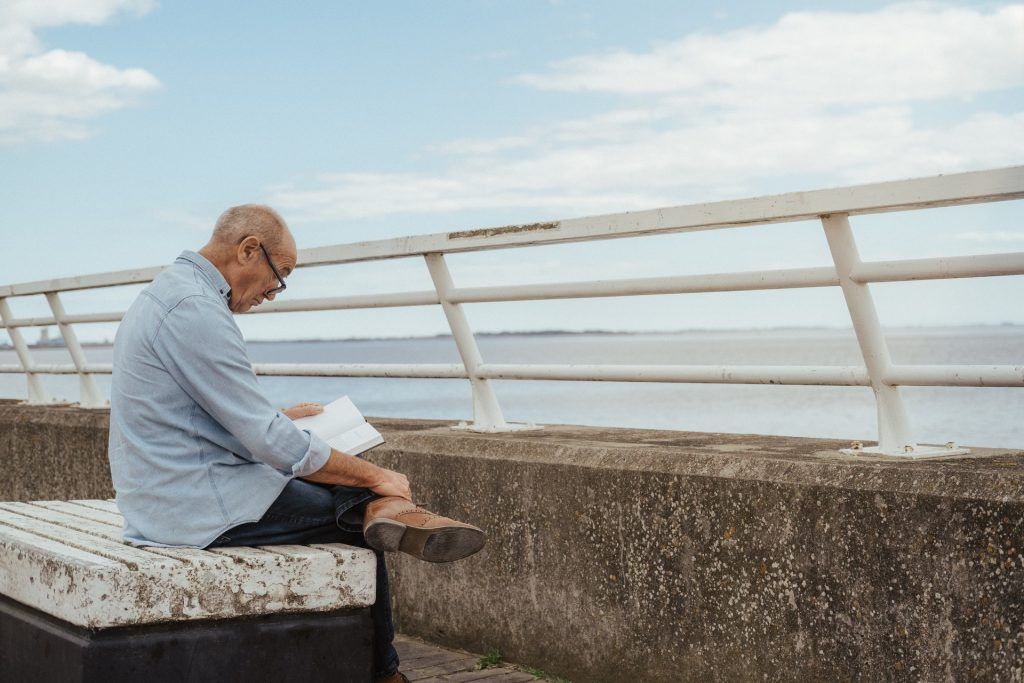Old man reading alone Hearing loss and depression with north london audiologists