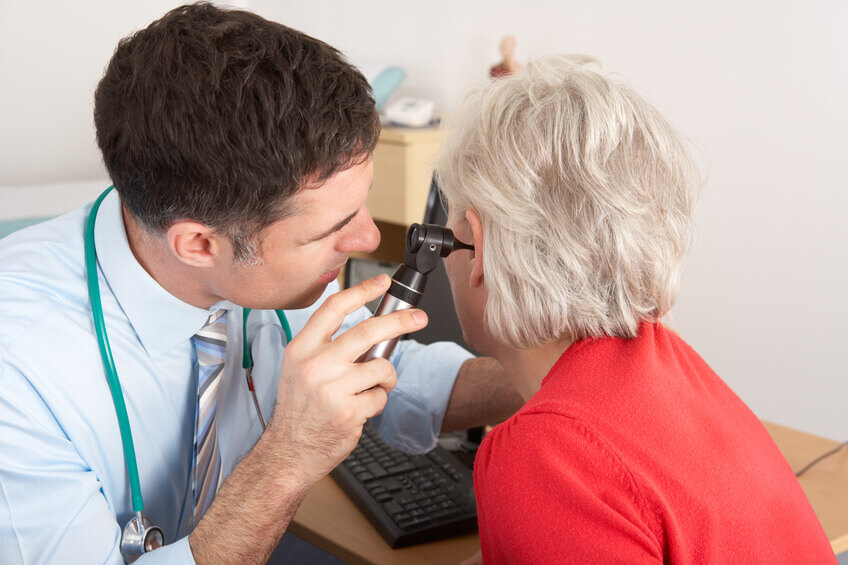 An audiologist conducting an in ear exam