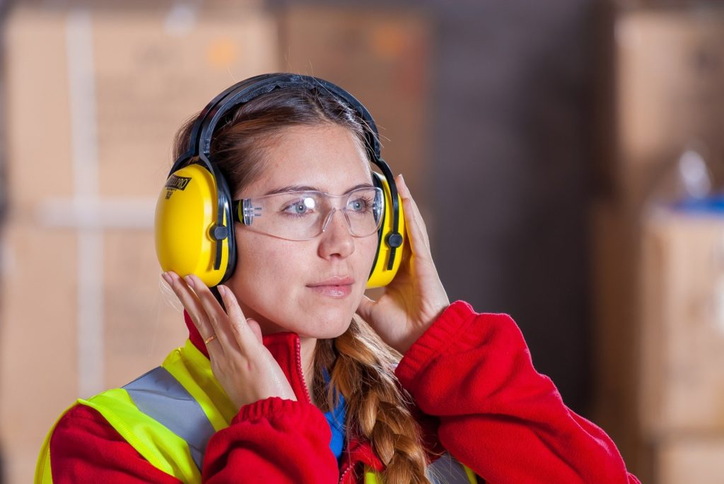 A professional woman using proper hearing protection to prevent tinnitus