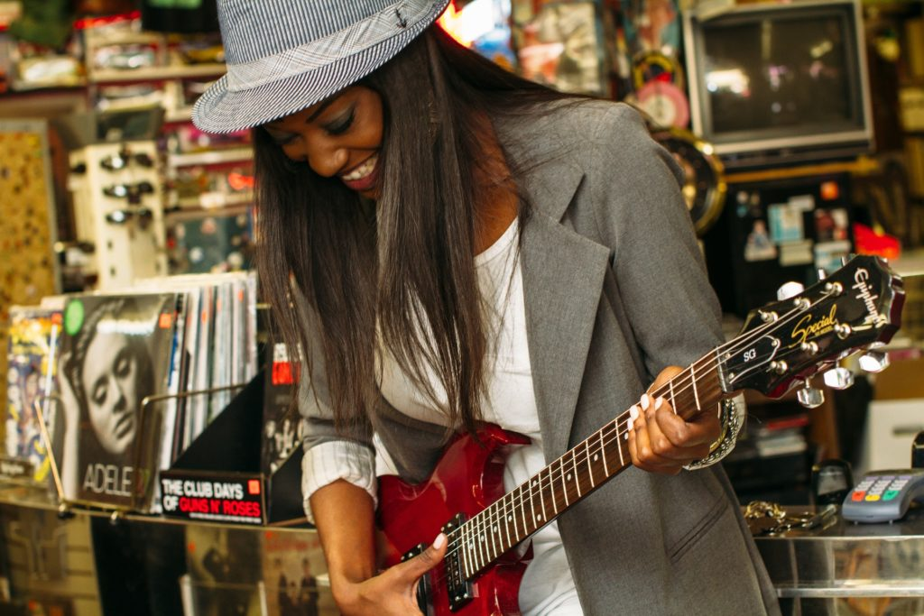 A young woman playing an electric guitar