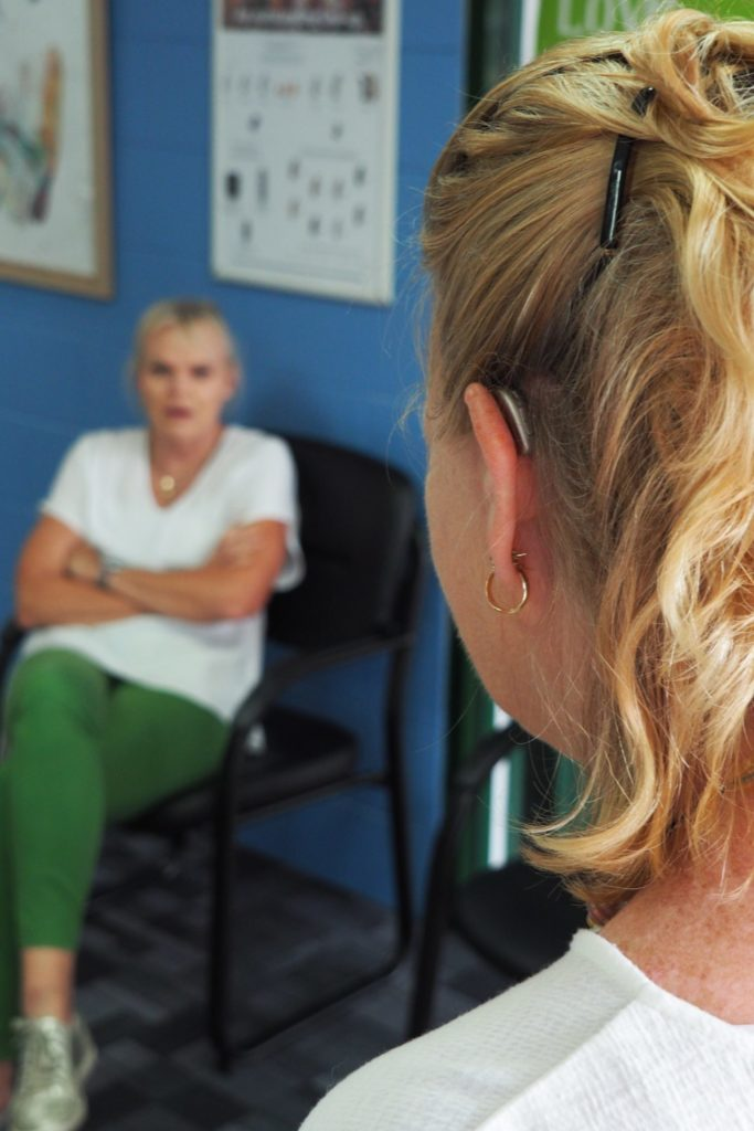 Woman in conversation with behind the ear hearing aid fitted
